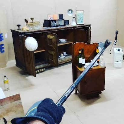 hand with crowbar pointing to objects in rage room